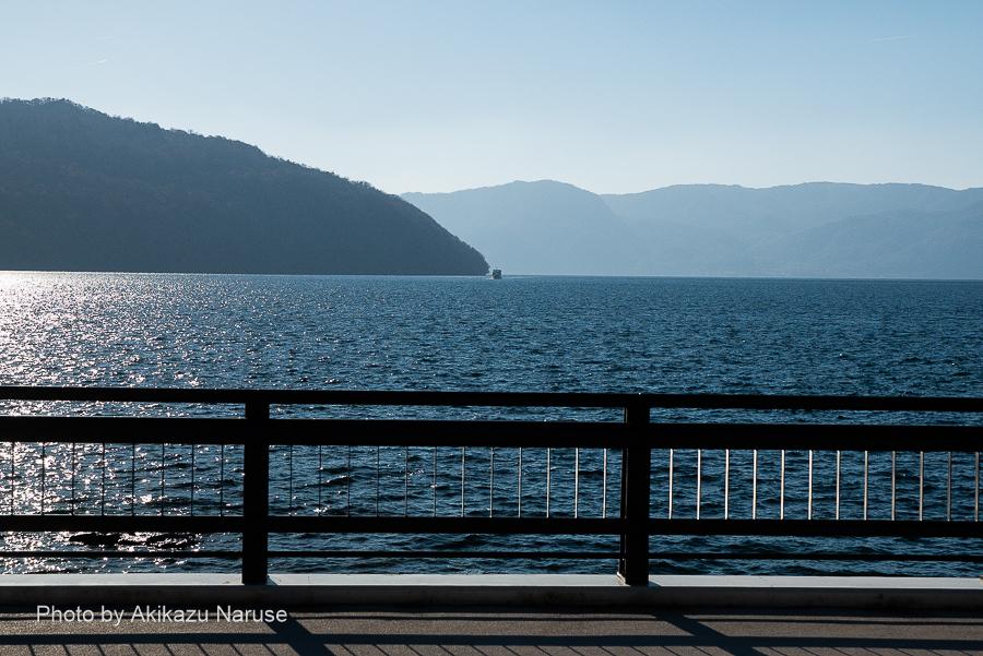十和田湖:奥入瀬渓流への流れはこの橋の下から始まる、左が御倉半島の先端にそびえる御倉山。画面中央部に小さく見えるのが遊覧船。逆光線で輝く辺り一帯が東湖(ひがしのうみ)。