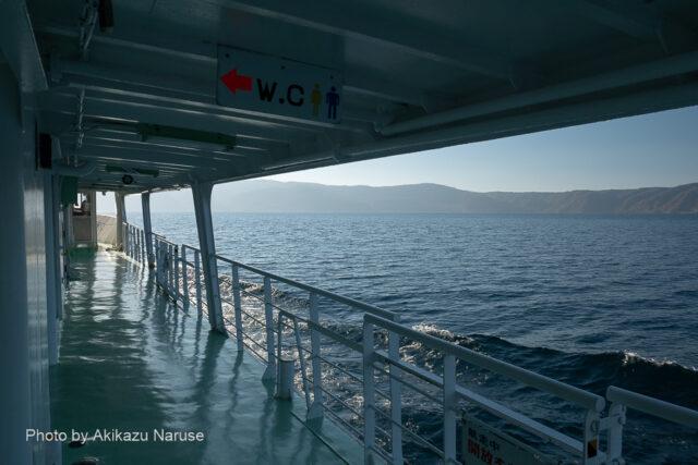 十和田湖:子ノ口港を出港した遊覧船は御倉半島の先端を目指して最短コースを航行。デッキに出て外輪山の北側を遠望する。